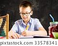 Boy doing math homework at home 33578341