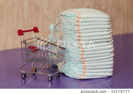 Stack of diapers or nappies and mini shopping cart 33578777