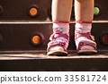 Baby legs in shoes and socks, standing on stairs 33581724