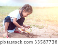 asian child girl having fun to play with sand 33587736
