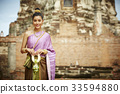 The picture of a woman in Thai costume standing and smiling near a pagoda. 33594880