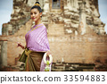The Thai woman is smiling and looking at something near the pagoda. 33594883