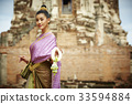 The Thai woman is smiling and looking at something near the pagoda. 33594884