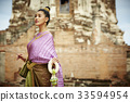 A picture of a Thai beautiful woman holding a garland in a pagoda 33594954