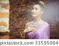 a Thai woman is putting her hand on her chest and looking at something 33595004
