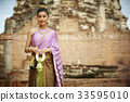 a portrait of a thai woman in traditional costume holding a garland and smiling 33595010