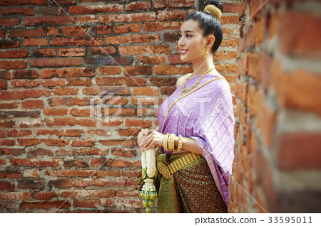a Thai woman is standing by brick wall, holding a garland and smiling 33595011