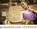 a female dancer in Thai traditional costume is performing outdoors 33595036