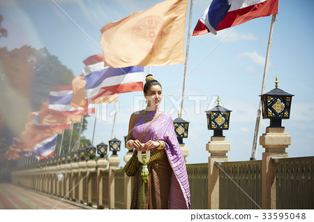 young woman in traditional costume is standing next to flags 33595048