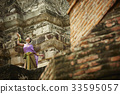 a thai woman is dancing in traditional costume at a temple 33595057