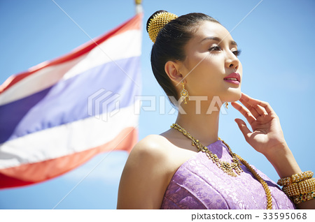 a portrait of beautiful thai woman posing with national flag 33595068