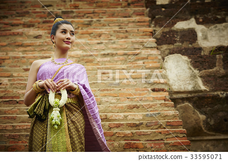 asian woman in thai traditional costume is standing at pagoda and looking away 33595071