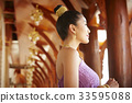 woman in thai dress is looking at something at temple 33595088