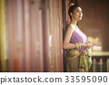 thai woman is leaning against wall and looking at something 33595090