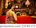 A Thai young girl is praying at a temple 33595172
