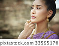 A Thai young woman is looking at something 33595176