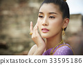 The portrait of Thai girl putting hand near the face 33595186