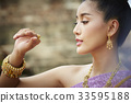 The portrait of a Thai woman looking at her hand 33595188