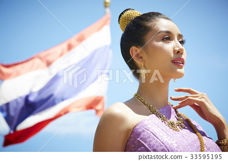 The portrait of a Thai girl standing and putting finger on her shoulder 33595195