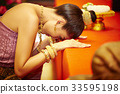 The picture of Thai girl doing kowtow in front of altar 33595198
