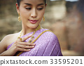 a portrait of a Thai girl touching her traditional costume and looking 33595201