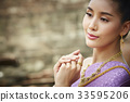 The portrait of a beautiful Thai girl thinking and smiling 33595206