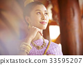 The portrait of Thai girl in Thai traditional costume smiling in hallway 33595207