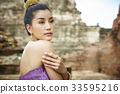 The portrait of a Thai girl hugging her arm and looking at something 33595216