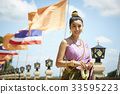 a Thai girl is standing, smiling and holding a garland 33595223