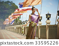 A Thai woman is standing on the balcony with flags in the morning. 33595226