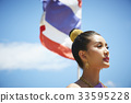 A photo of beautiful Thai woman looking something in the sky. 33595228