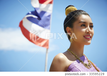 A Thai young woman is smiling happily beside the flag. 33595229