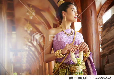 A Thai young woman is walking through the balcony while holding Thai ornament. 33595232