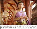 A Thai young woman is standing beside the ancient pillar while holding the Thai ornament. 33595245