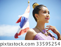 A beautiful Thai woman is touching her necklace while smiling happily. 33595254