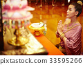 A beautiful Thai woman is staring at the altar while praying. 33595266