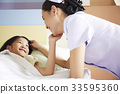 A nurse is talking cheerfully to a kid patient 33595360
