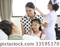 An old patient is talking cheerfully to her relatives in a hospital 33595370