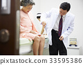a doctor is checking elderly woman's knee jerk in clinic 33595386
