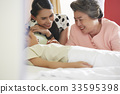 mother and grandmother are smiling and taking care of little girl 33595398