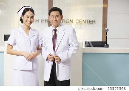 A photo of a nurse and a doctor standing at a reception in hospital. 33595568