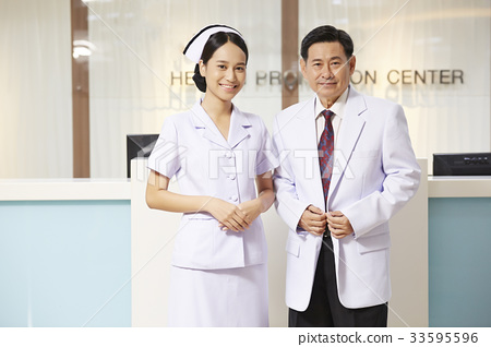 a picture of a doctor and a nurse standing and smiling in the health center 33595596