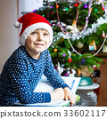 little school kid boy reading a book on Christmas 33602117