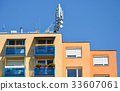 Antennas on the top of an apartment building 33607061