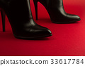 high heel black shoes on red background 33617784