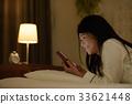 ผู้หญิงกำลังดูสมาร์ทโฟนนอนอยู่บนเตียง 33621448