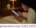 침대에서 스마트 폰을 보는 여자 33621450
