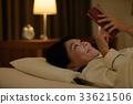 침대에서 스마트 폰을 보는 젊은 여성 33621506