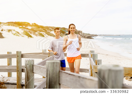 Runners. Young couple running on beach 33630982