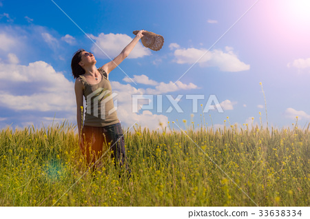 Young woman with hat enjoying the nature.  33638334